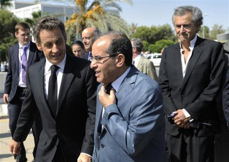 France's President Sarkozy speaks with (NTC) Prime Minister Mahmoud Jibril as they walk to Medical Center in Tripoli